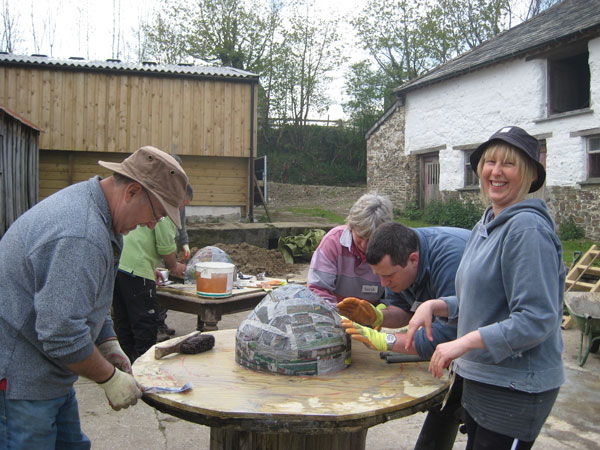 Group of people building a cob oven on the build your own pizza oven course at South Yeo Farm West, Devon